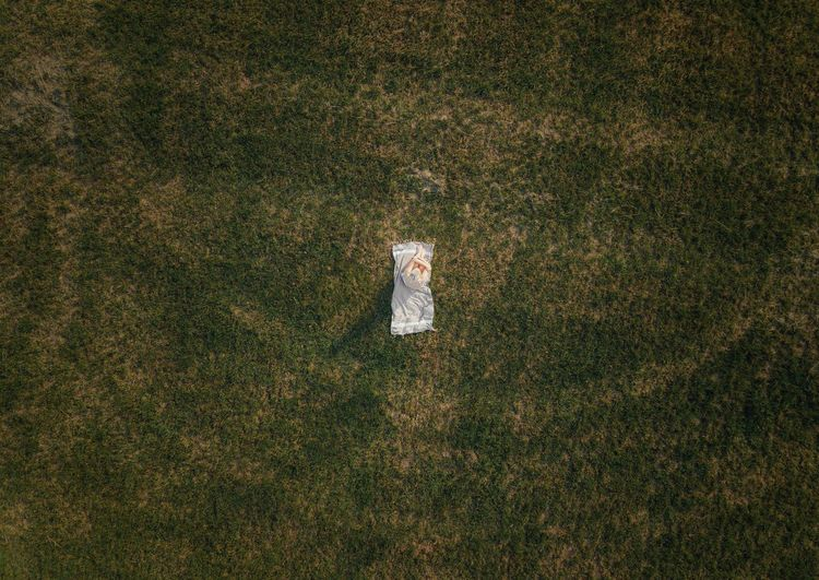 Drone shot of woman sitting on picnic blanket