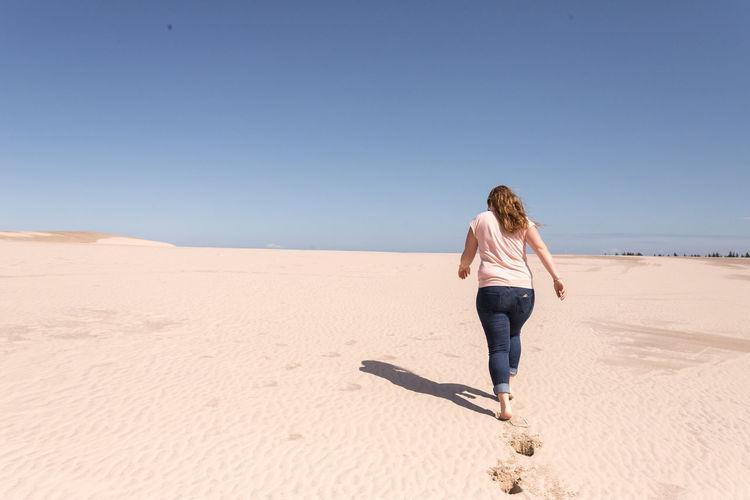 Full length of woman on sand at beach against clear sky