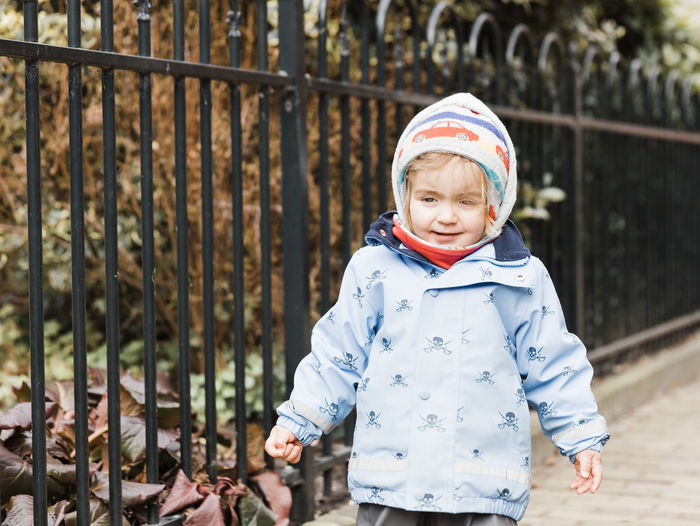 Portrait Of Baby Girl Wearing Warm Clothing While Standing Against Fence