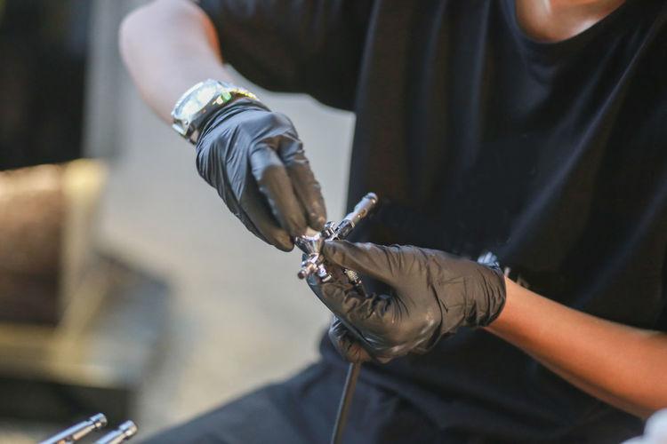 Midsection Of Man Repairing Equipment In Workshop