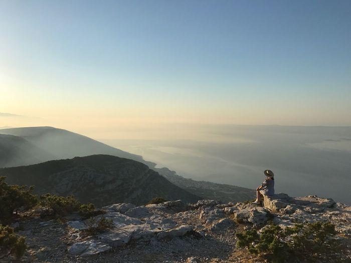 Female hiker sitting on mountain against blue sky