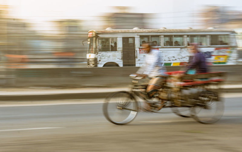 Blurred motion of man riding bicycle against bus on road in city