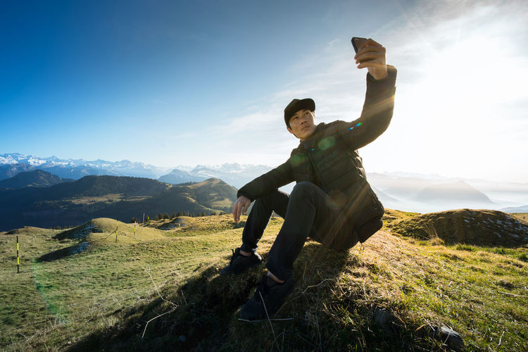 Man Taking Selfie Through Mobile Phone On Field Against Sky