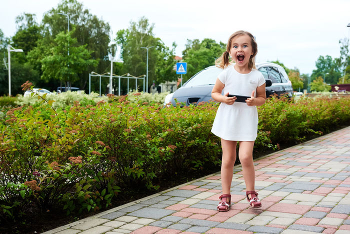 Adorable expressive little girl with a smartphone outdoors 5 Years Old Alone Beautiful Caucasian Cell Cellphone Child Daughter Device Emotions Expression Fun Game Gaming Leisure Little Girl Mobile Phone Outdoors Phone Play Player Small Girl Smartphone Summer Technology