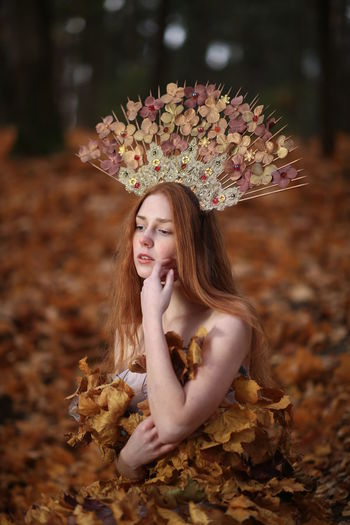 Thoughtful young woman covered with leaves sitting at forest during autumn