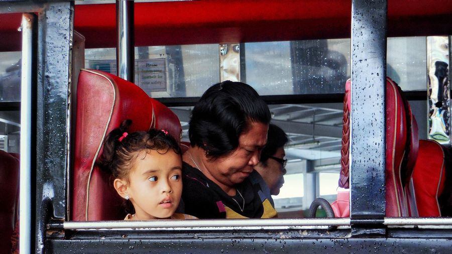 Girl looking through window while sitting in bus