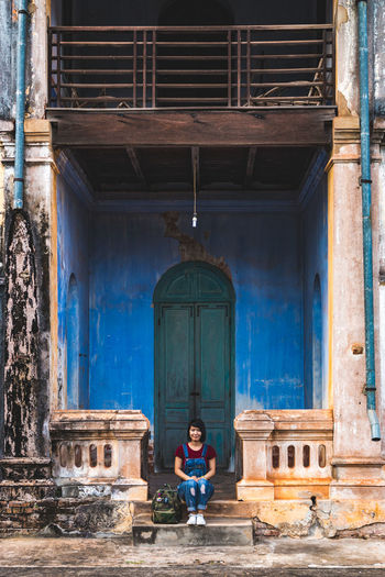 Full length of woman sitting against old house