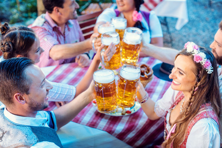High angle view of friends toasting beer while sitting at restaurant