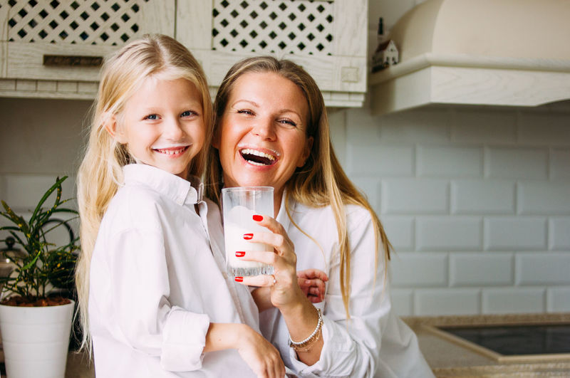 Portrait of happy mother and daughter in kitchen at home
