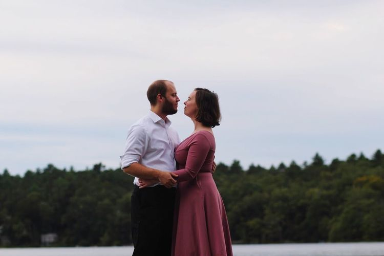 Side view of couple kissing against sky