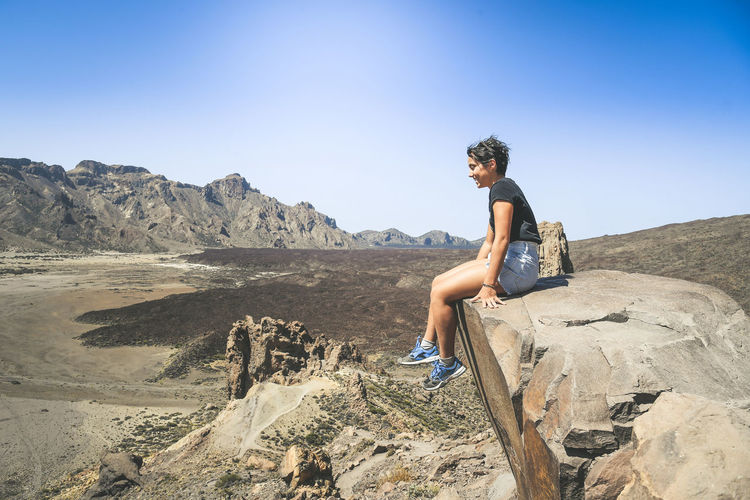 Side view of smiling teenage girl sitting on cliff against blue sky