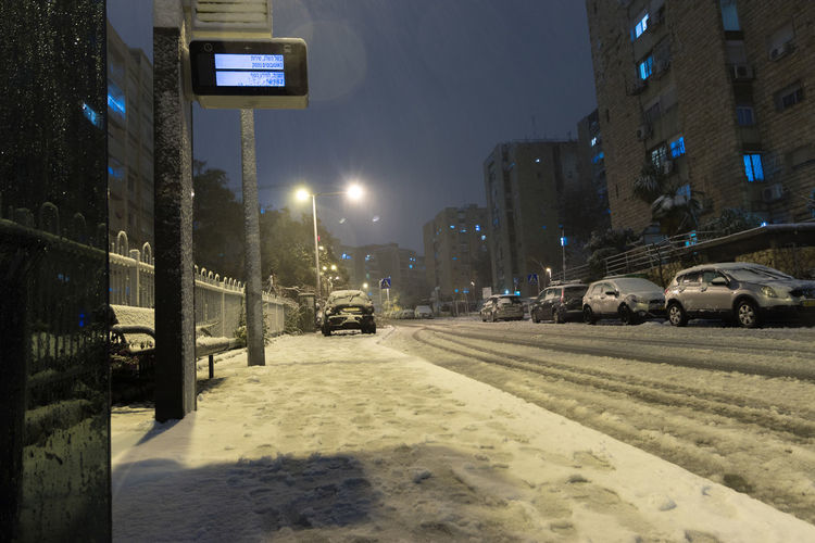 Cars on road amidst buildings in city during winter