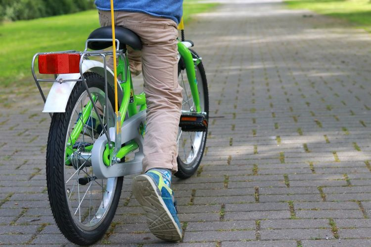 Low section of boy riding bicycle on footpath