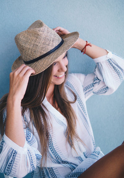 Woman wearing hat sitting on chair against wall