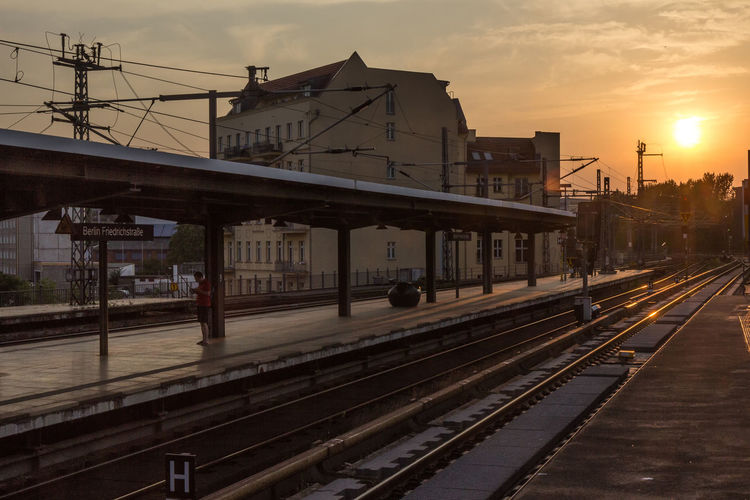 Railway tracks in city against sky at sunset