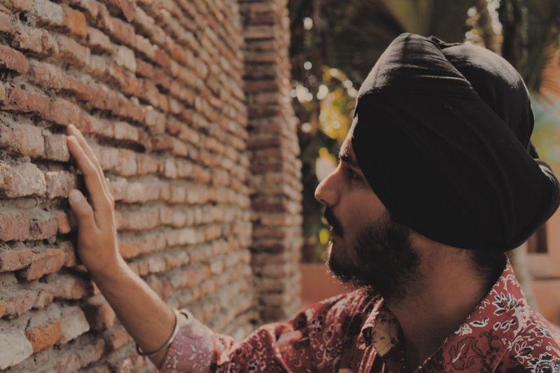 Young man touching brick wall
