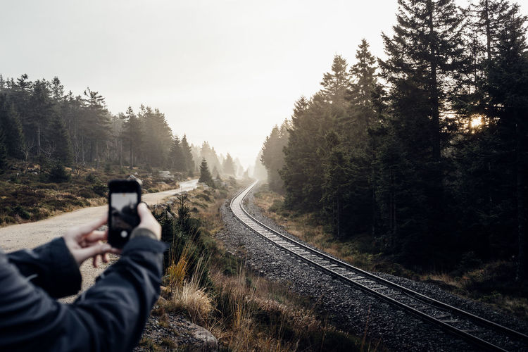Cropped hands of man photographing railroad tracks against clear sky
