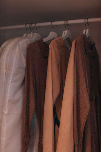 Clothes in beige and brown autumn colors hanging on a hanger in the closet