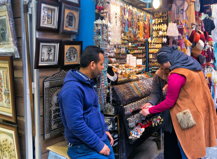TUNIS, TUNISIA - APRIL 3: Women buy accessories in the traditional market in the Medina in Tunis, Tunisia on April 3, 2018. Men Store Market Business Customer  Buying Shopping People Sale Women Retail  Tunisia Tunis Medina Old Arabic Street Accessories Ornaments Souvenir Gift Silver  Seller Vendors Hat