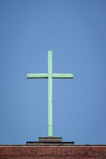Cross on top of a church in front of a blue sky Cross Religion Blue Clear Sky Belief Sky Spirituality No People Copy Space Day Nature Architecture Low Angle View Built Structure Place Of Worship Outdoors Symbol Sunlight Religious Equipment