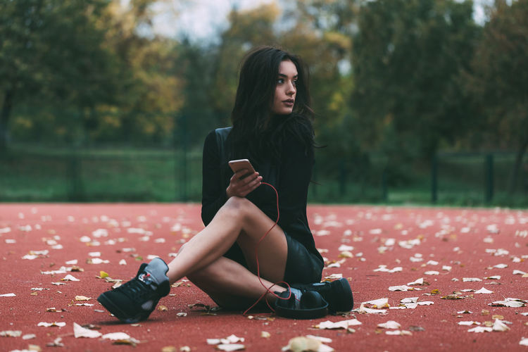 Autumn Beautiful Woman Day Focus On Foreground Full Length Leaf Leisure Activity Lifestyles Mobile Phone Nature One Person Outdoors Park - Man Made Space People Portable Information Device Real People Sitting Technology Tree Wireless Technology Young Adult Young Women