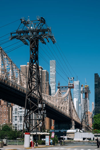 New York City - USA - May 15 2019: Queensboro bridge and tramway of Manhattan midtown on Roosevelt Island East River Landscape America Architecture Blue Bridge Building Cable City Cityscape Day Downtown East Famous Garden Island Landmark Lifestyle Manhattan Midtown Modern New New York City NY NYC Panoramic Park Queensboro River Roosevelt Roosevelt Island Scenic Sky Skyline Skyscraper Spring Street Sunny Tourism Tower Tram Tramway Transportation Travel Urban USA View Water Waterfront York