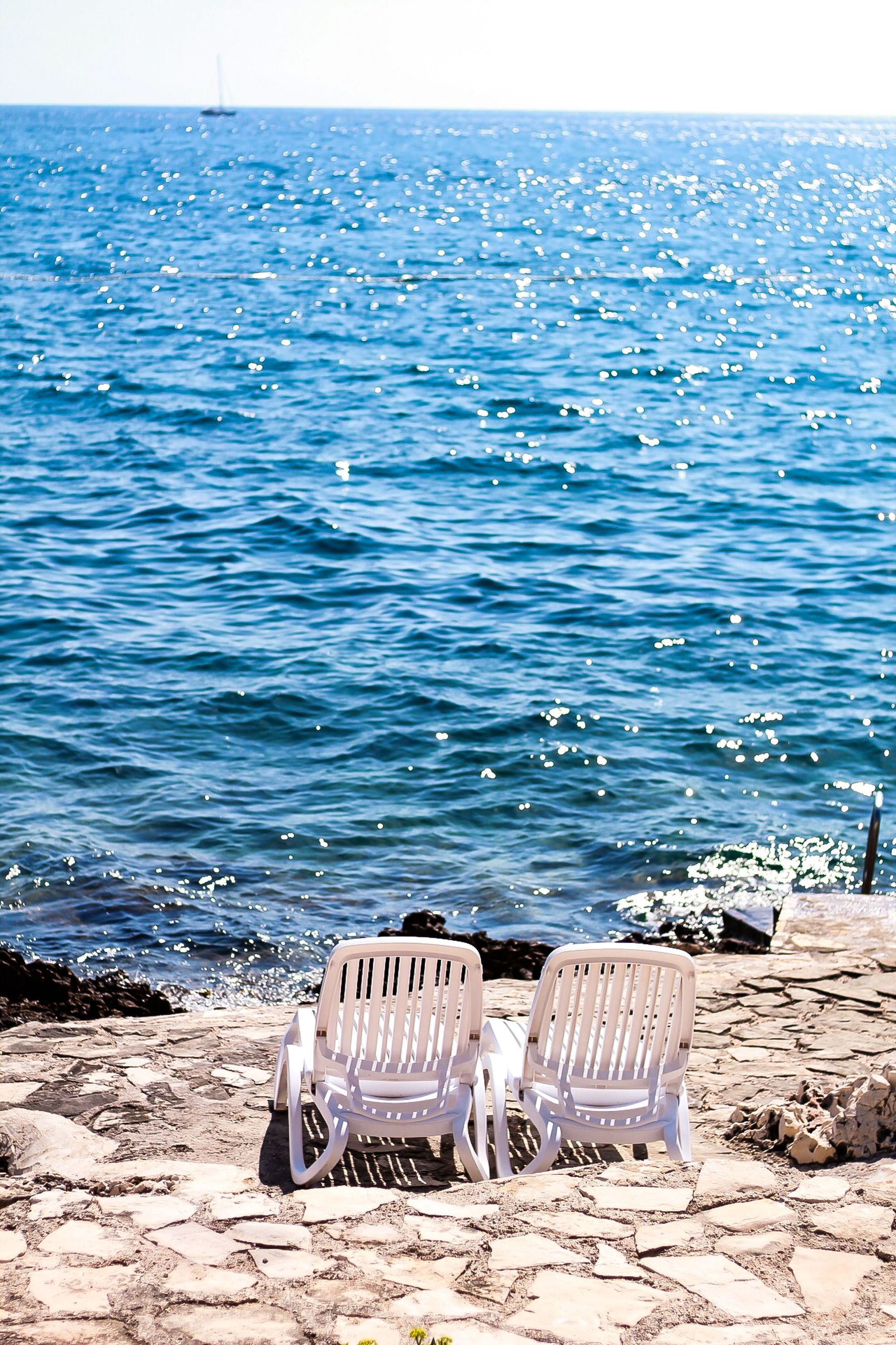 water, sea, horizon over water, beach, horizon, beauty in nature, tranquility, tranquil scene, nature, sky, chair, land, scenics - nature, sand, absence, idyllic, day, sunlight, seat, no people, outdoors