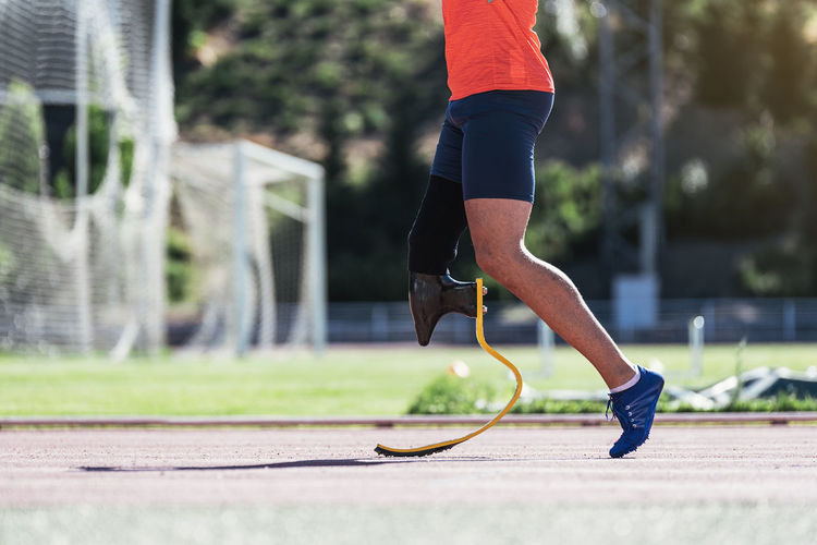 Low section of athlete with prosthetic leg on running track