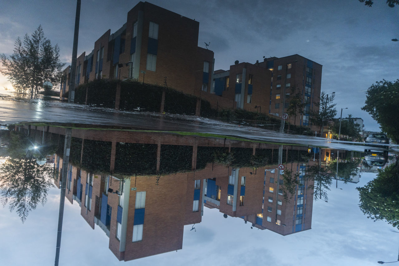 REFLECTION OF BUILDINGS IN PUDDLE ON STREET IN CITY