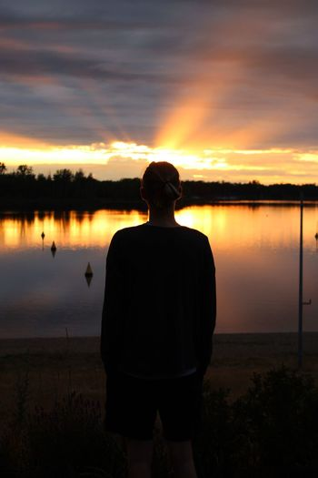 Rear view of silhouette man standing by lake against sky during sunset