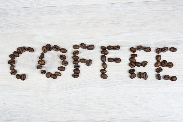 the text coffee made of coffee beans Coffee Background Brown Close-up Coffee Bean Day Food Food And Drink Freshness Indoors  Large Group Of Objects Love No People Raw Coffee Bean Roasted Coffee Bean Text White Background Wooden Texture