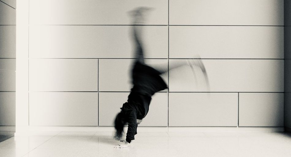 Low section of man walking on floor against wall