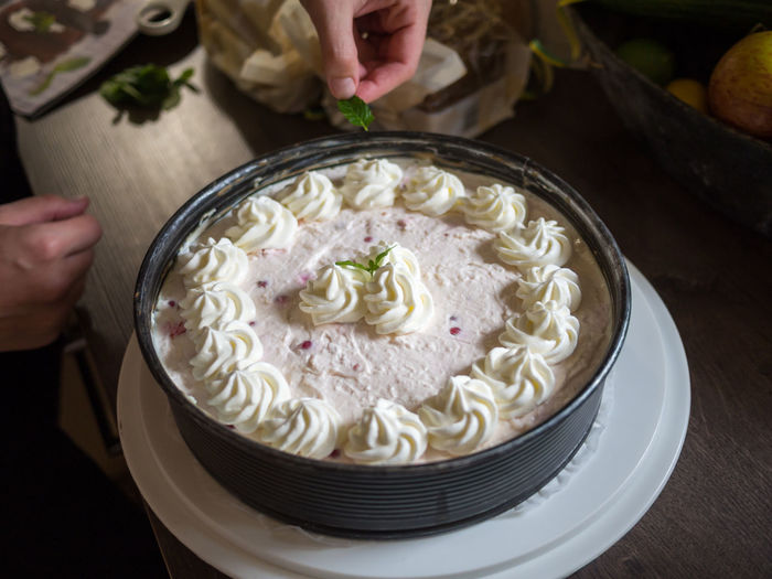 Human Hands Decorating Cream Pie With Mint Leaves