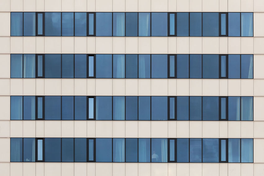 Close-up of the window front of a modern hotel Beige In A Row Abundance Architecture Backgrounds Black Color Blue Building Exterior Built Structure City Close-up Concrete Day Full Frame Geometric Shape Glass - Material Modern No People Office Building Exterior Outdoors Pattern Rectangle Repetition Wall - Building Feature Window