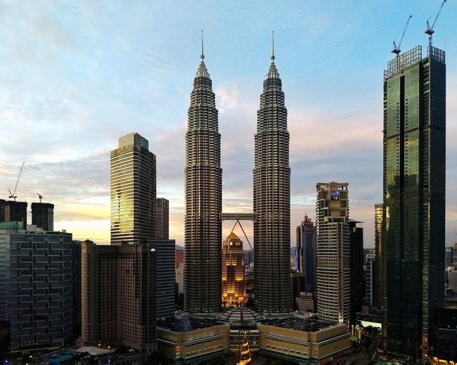 Kuala Lumpur city centre at sunset Maxis Tower Petronas Twin Towers KLCC Twin Towers Suria KLCC Four Seasons Hotel Skyscraper Modern Building Exterior Sunset Architecture Travel Destinations Illuminated Urban Skyline Sky Cloud - Sky Cityscape Outdoors City No People Day