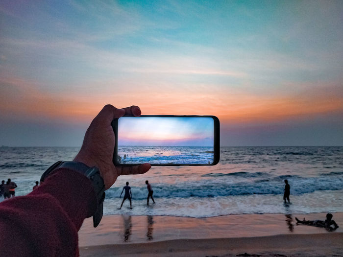 Man photographing at beach against sky during sunset