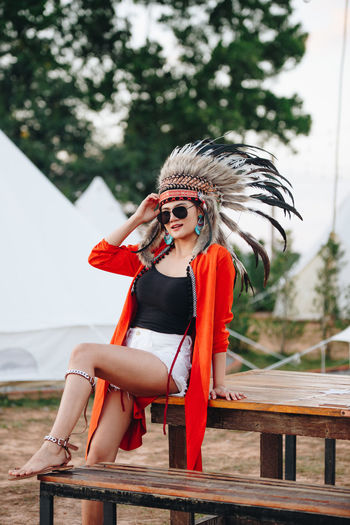 Portrait of young woman wearing headdress while sitting on picnic table