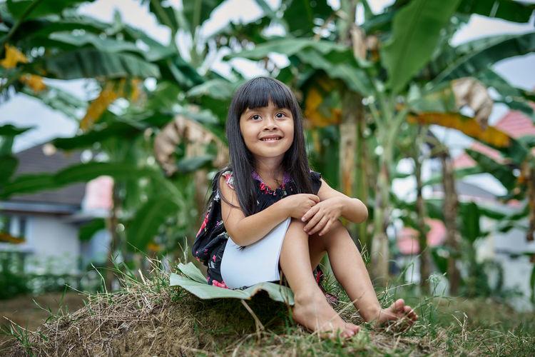 Portrait of smiling girl sitting on land