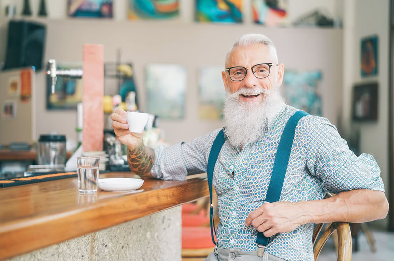 Portrait of senior man wearing glasses holding cup on table