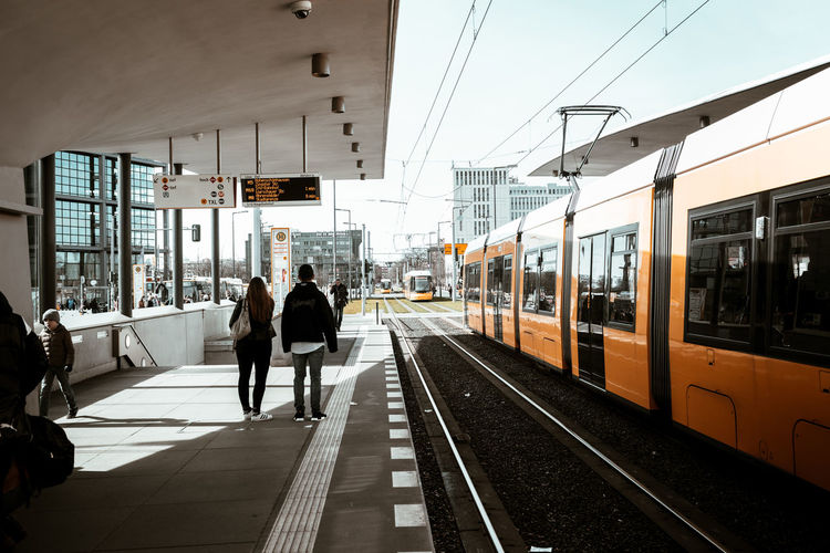 People on railroad station platform in city