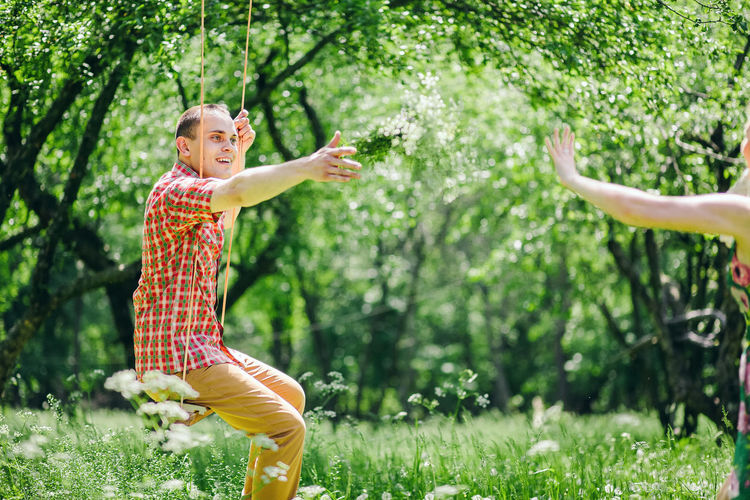 couple relax together in summer forest with swing background. Summer time in green meadow. Outdoors Together Love Dating Couple Relationship Relaxing Leisure Activity Lifestyles Lifestyle Two People Field Green Grass colour of life Picnic Forest Wildflower Summer Spring Happiness Smiling Casual Clothing Emotion Tree Real People One Person Plant Positive Emotion