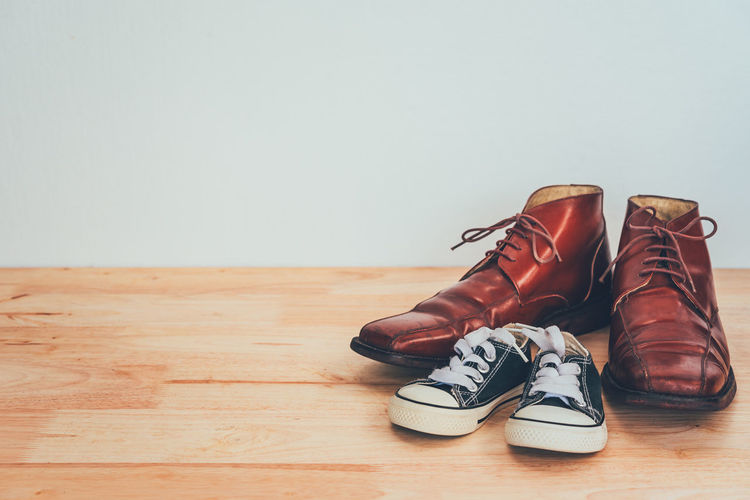 Close-up of shoes on hardwood floor against wall