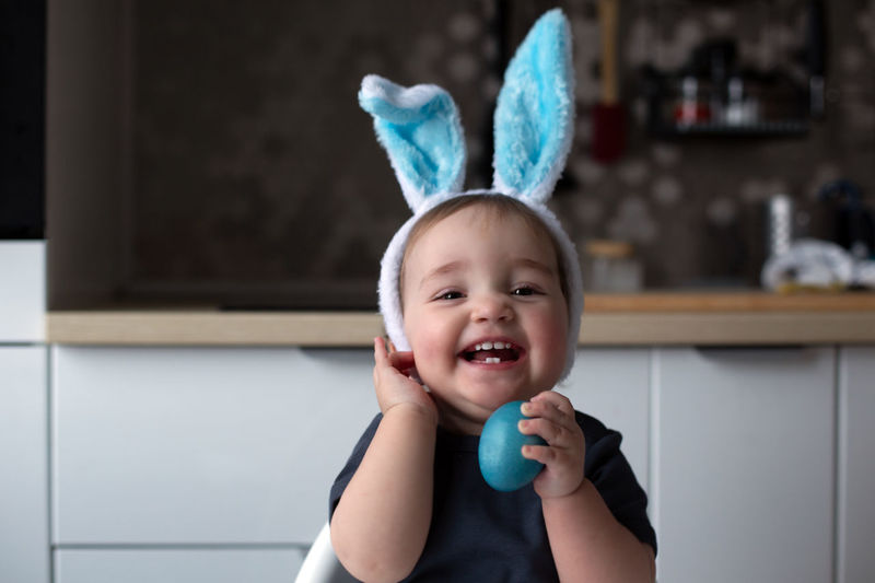 Cheerful laughing baby wearing blue bunny ears and holding blue easter egg. lifestyle, copy space