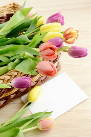 Close-up of tulips in basket with greeting card on table