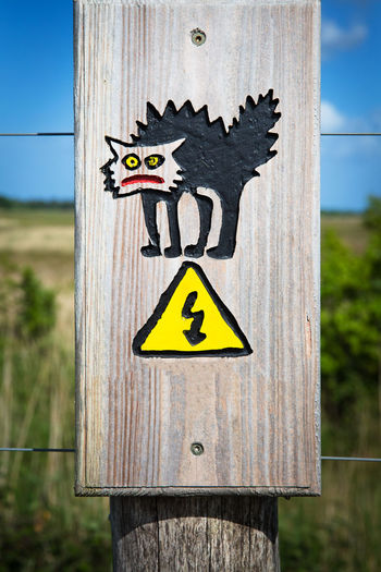 Close-up of sign on wooden post