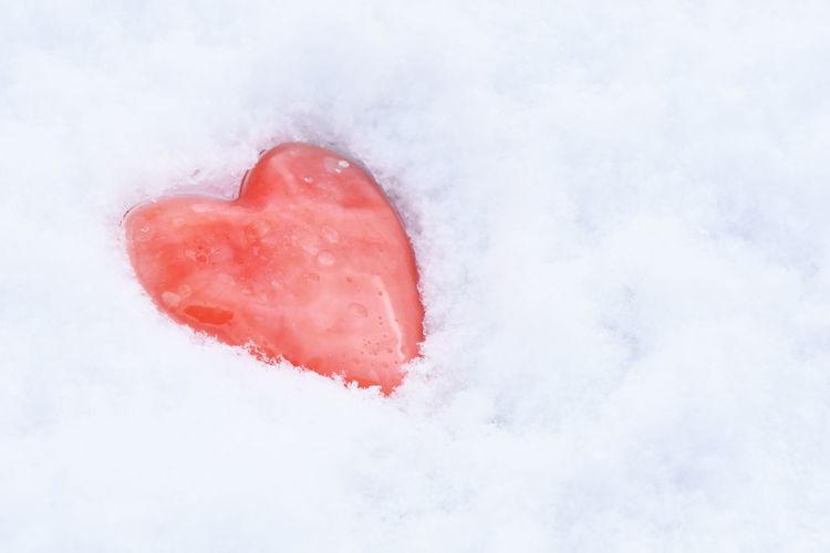 Red heart shape decoration on snowy field