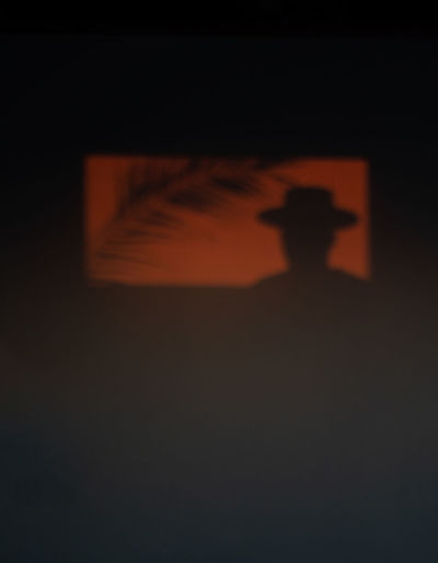 Silhouette person shadow against orange sky