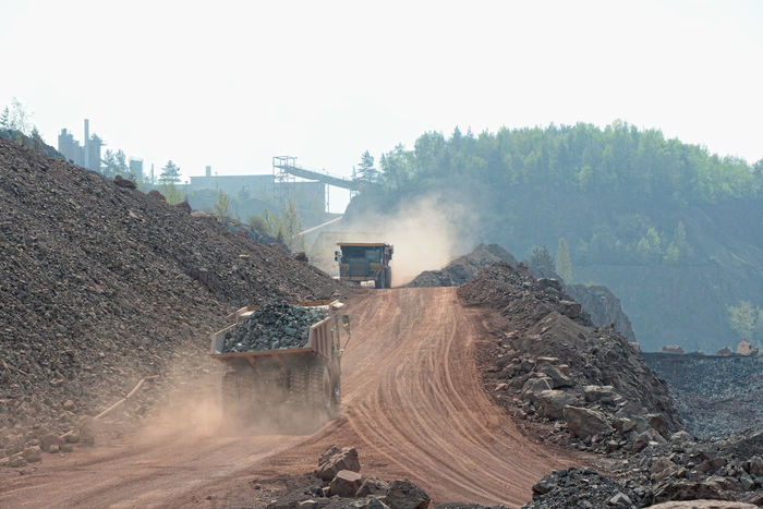 two dumper trucks with loaded stones driving along in a quarry. mining industry Quarry Quarry Rock Stonepit Stone Pit Steinbruch Dumper Dumper Truck Loading Rocks Construction Material Construction Materials Transportation Steinbrecher Stone Crusher Driving Dust Production