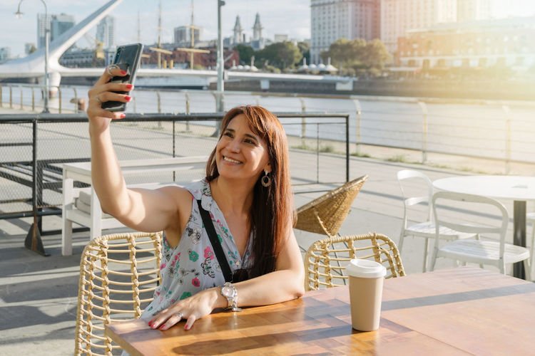 Portrait of young woman photographing with mobile phone in city
