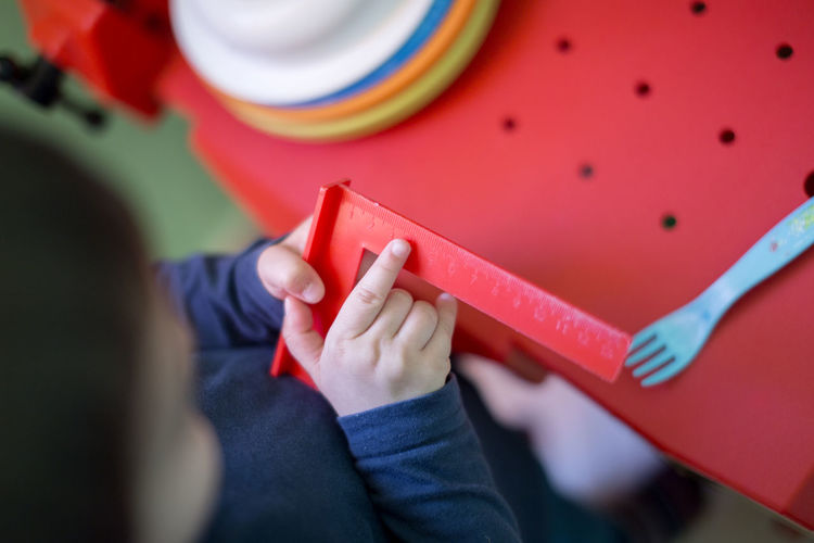 High angle view of boy playing with ruler at home